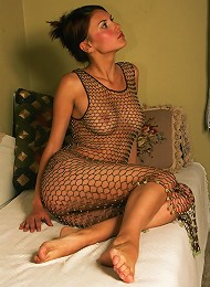 Beautiful nude girl posing in a fishnet dress