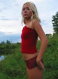 Young blonde turns down her red panties and relaxes on the riverside.